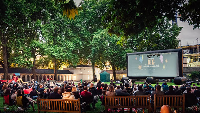 People sit on park benches and blankets under a canopy of trees as they watch the Big Lebowski on a big screen.