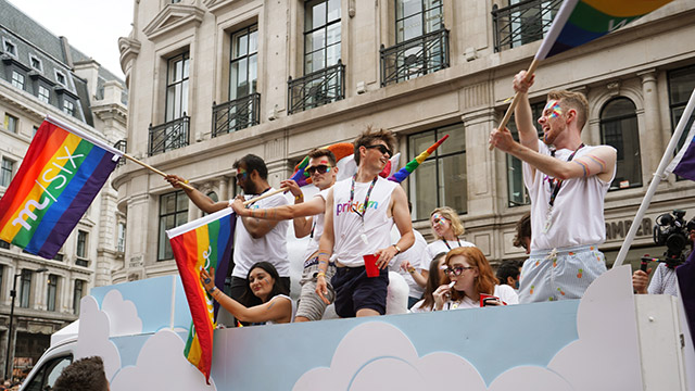 People standing up on a float, waving rainbow flags, as they travel along during the Pride in London parade.