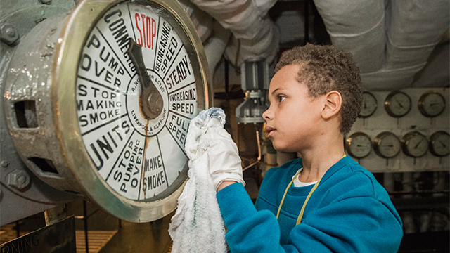 A boy helps to clean a gauge on HMS Belfast, as part of the Ship Shape activities.