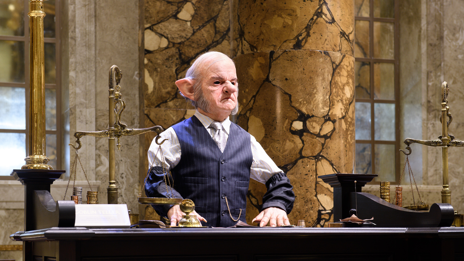 A goblin figure stands behind a bank desk as part of the set of the Gringotts Wizarding Bank display.