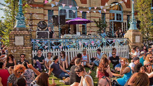 People sit on grass under the sun in front of a DJ set at Alexandra Palace.