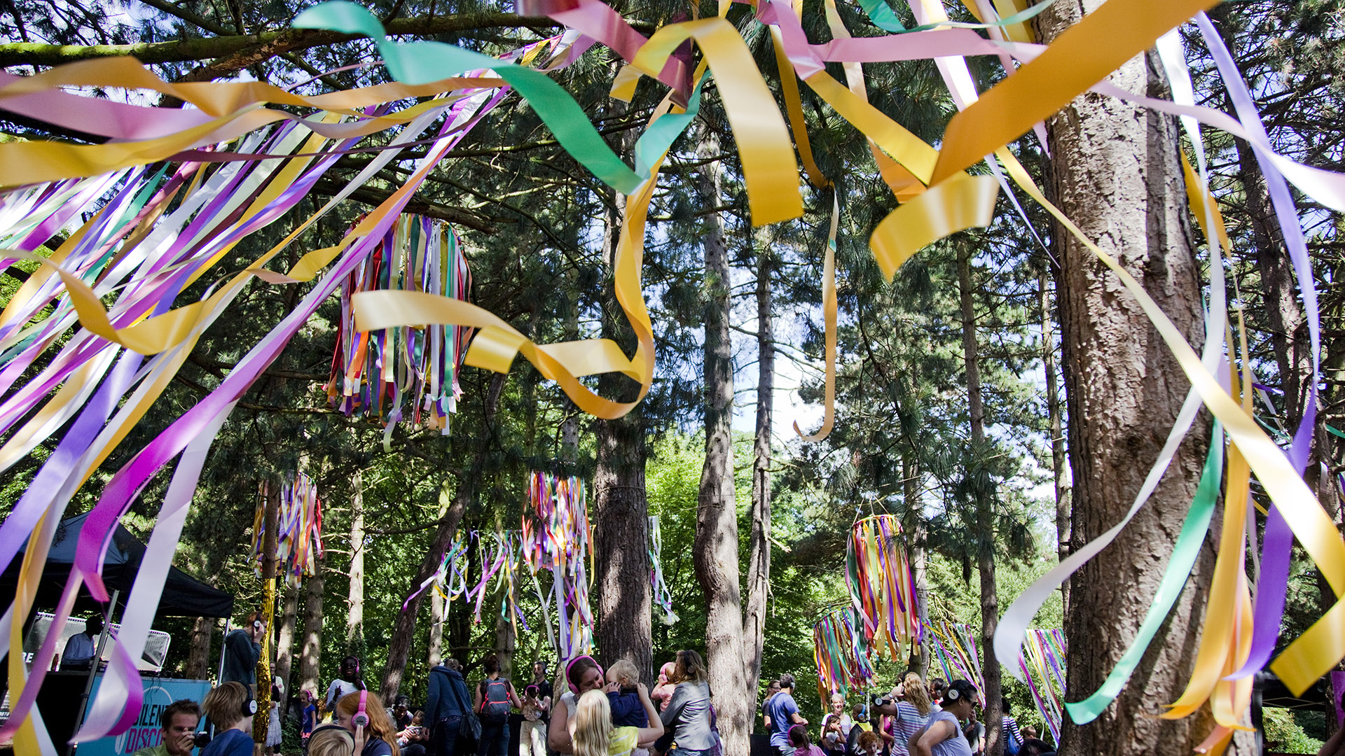 Colourful ribbons fill a wood where a silent disco is taking place.