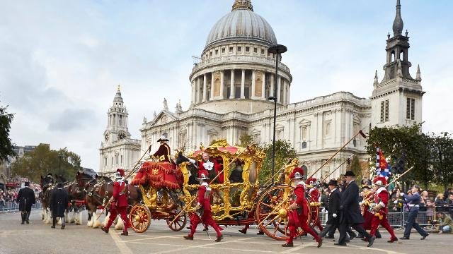 A golden carriage, manned by people in traditional red livery, passes in front of St Paul's Cathedral.