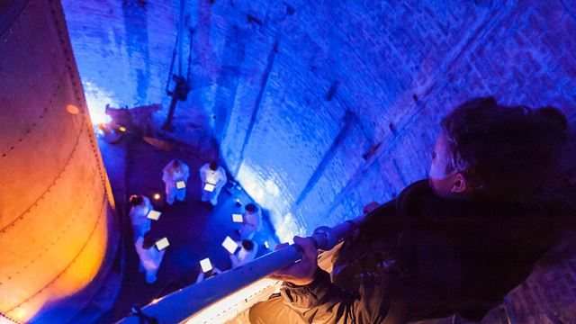 A man looks down at a choir performing in the bascule chambers of Tower Bridge.