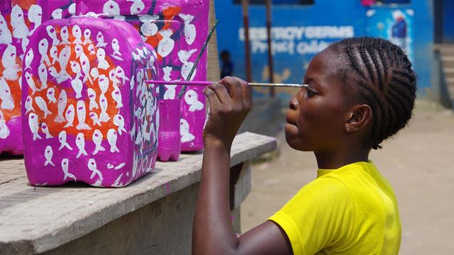 A child with a paintbrush paints a jerry can purple with white fish.