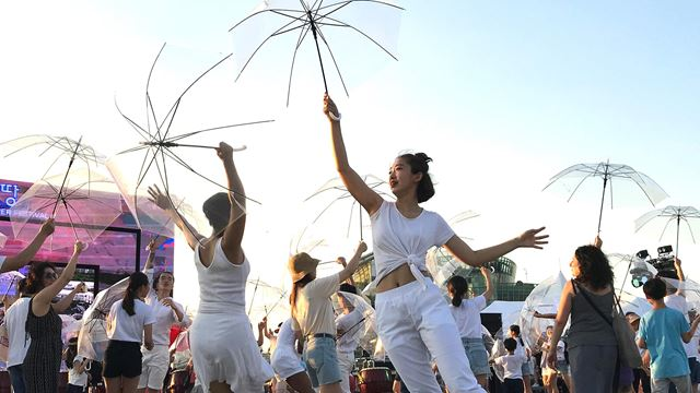 Performers hold transparent umbrellas in the air as part of the Red Umbrella dance show.