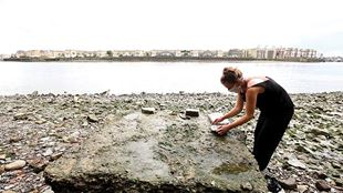 A woman studies items on the rocky foreshore of the Thames, with the river and the other riverbank in the background.
