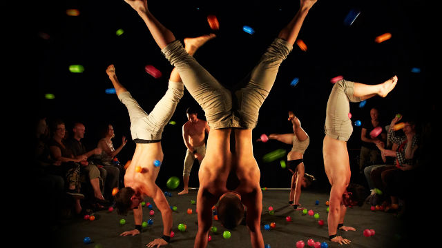 Performers from Australian circus troupe Gravity and Other Myths perform handstands in a circle on a stage.