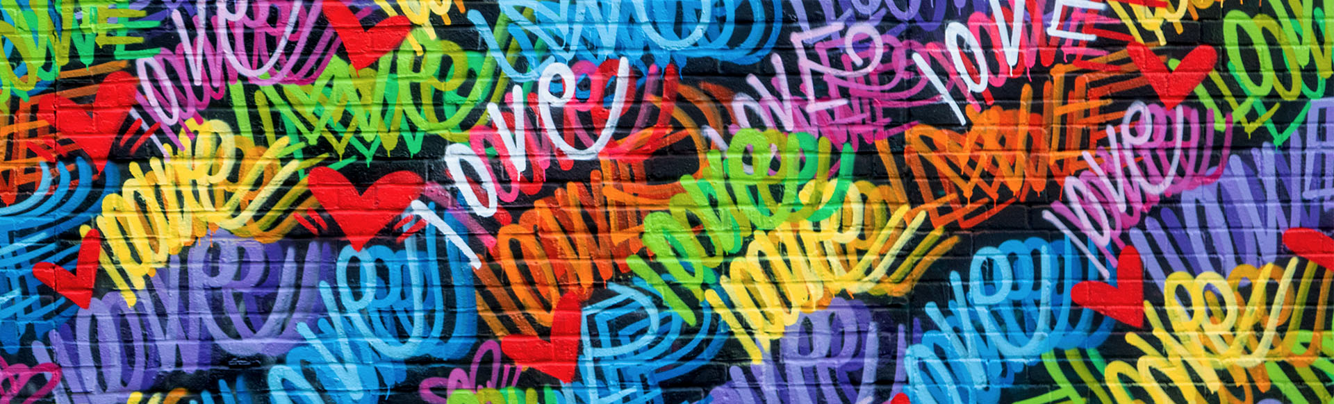 Close up of street art in Shoreditch featuring spray painted hearts and the word love in different colours.