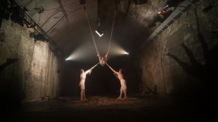 Two acrobats hold another acrobat in a trapeze on stage in the low-lit surrounds of The Vaults, during VAULT Festival.