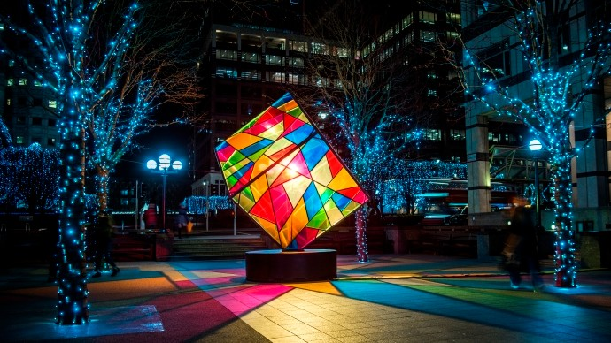A geometric, colourful cube exhibit, Colour Cubed by Mandylights, Wren Landing, lighting up Canary Wharf.