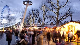 Shoppers mingle among the lit huts at the Winter Market at Southbank Centre.