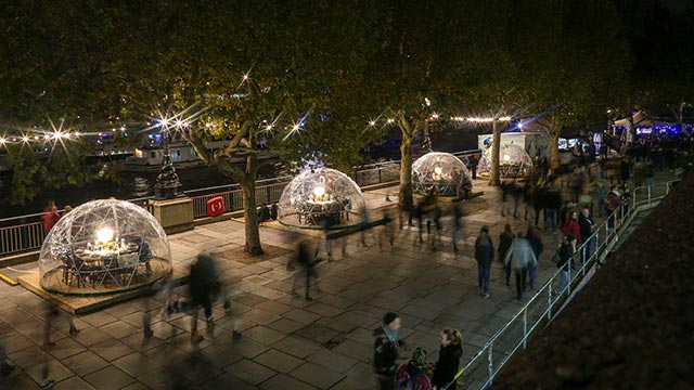 "A night-time panoramic view of clear plastic domes ""snow globes"", with tables and chairs inside, along the South Bank."