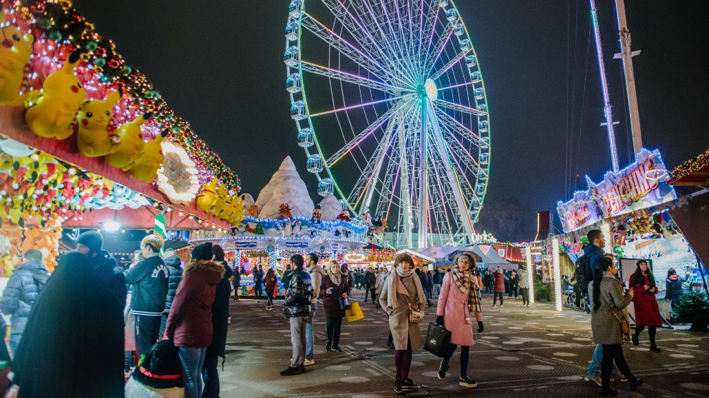 People wandering around the stalls of the Winter Wonderland with a Ferris Wheel in the background.