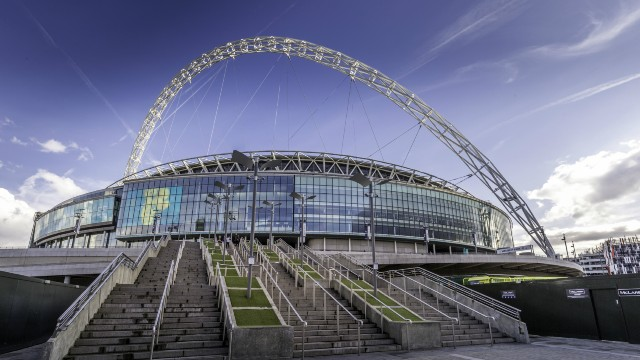 The outside of Wembley Stadium viewed from the bottom of the entrance steps with the venue's iconic arch emphasised against the blue sky.