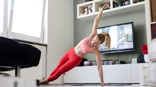 Woman wearing sports attire works out in her home via an online fitness class playing on the TV in the background.