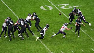 Action shot of 12 NFL players against the bright green pitch and 20 line during Houston Texans at Jacksonville Jaguars game.