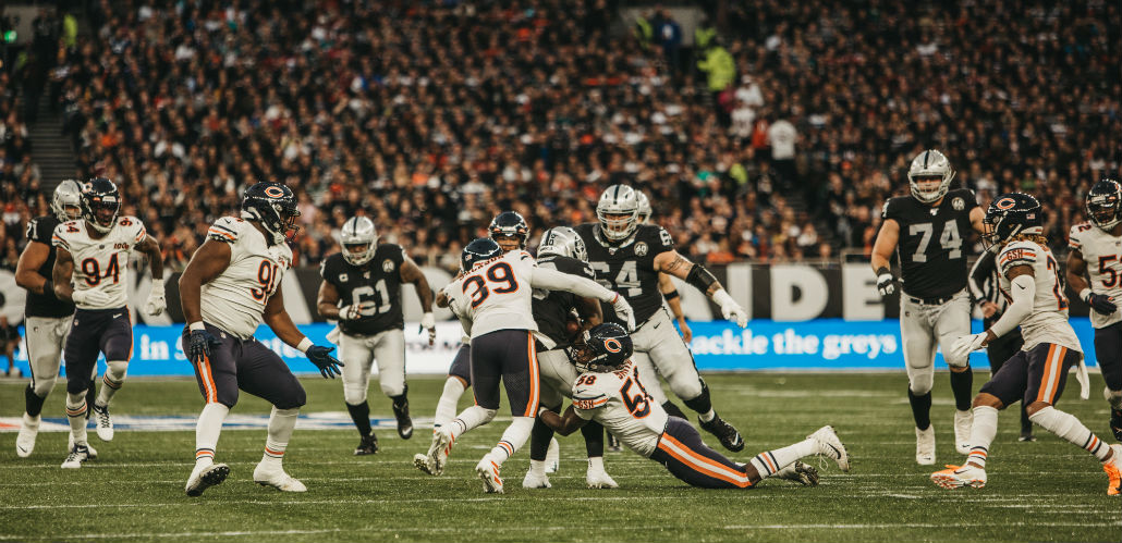 Action shot of seven players from Oakland Raiders and Chicago Bears game at Tottenham Hotspur Stadium. Image courtesy of Hamish Jordan and NFL UK.