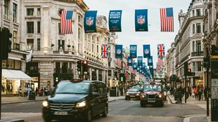 Banners for the NFL London games hang along Regent Street over black cabs.