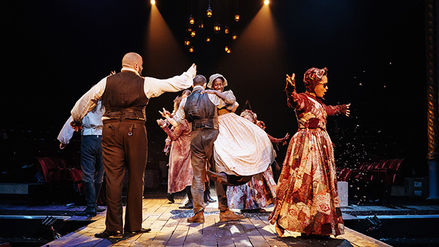 Cast members, dressed in Victorian clothing, on stage at The Old Vic.