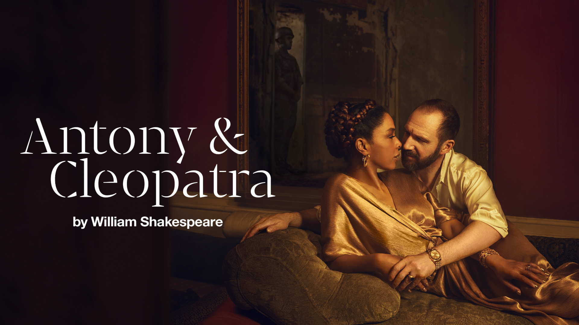 Antony and Cleopatra by William Shakespeare written in white, to the left of Sophie Okonedo and Ralph Fiennes, who embrace while laying down