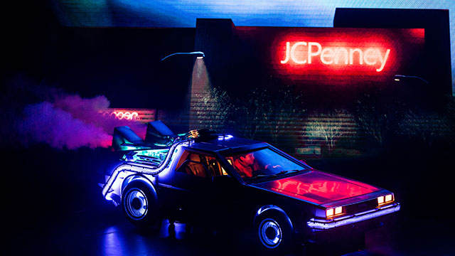 Marty McFly drives his car in the dark under blue and red lights