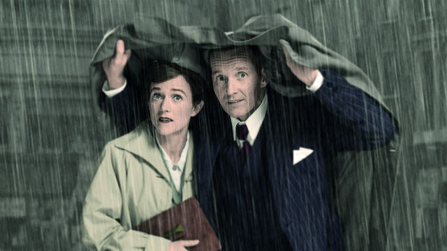 Man and woman sheltering underneath coat in the rain in Brief Encounter.