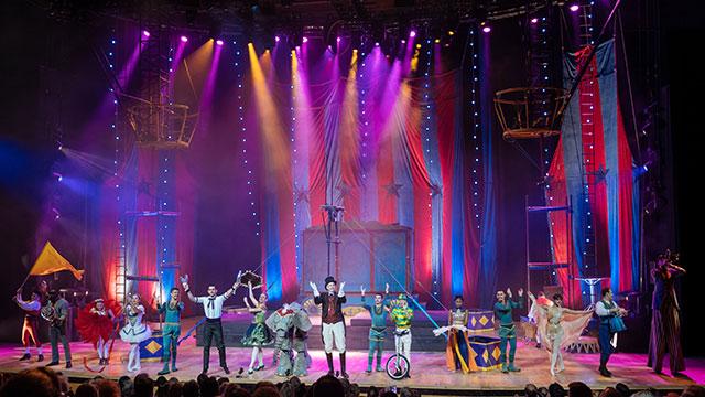 """Актеры """"Цирка 1903"""" на сцене под фиолетовым и оранжевым светом."""