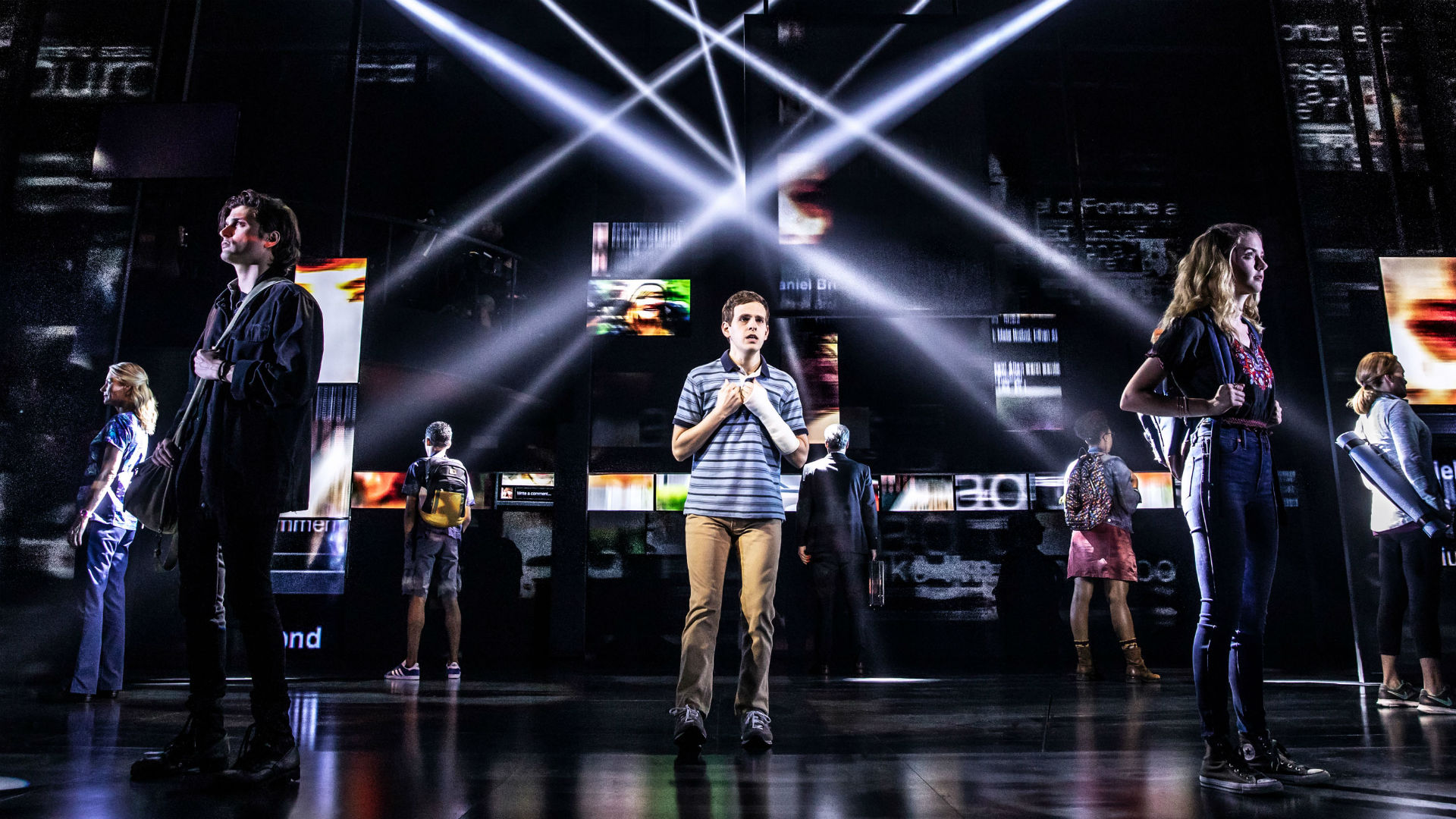 A group of people stand around Evan Hansen on a dark stage while lights beam around the cast
