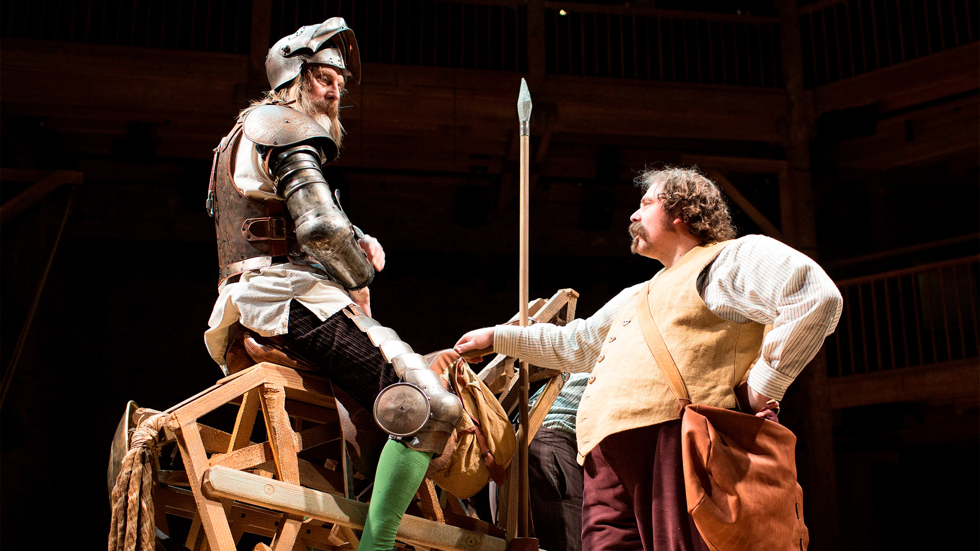 Dressed in armour, David Threlfall sits on a wooden horse as Rufus Hound stands below, leaning against the horse.