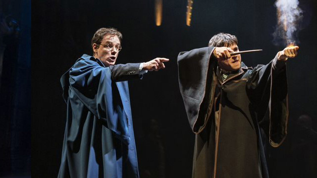 Two actors on stage performing magic at Harry Potter and the Cursed Child.
