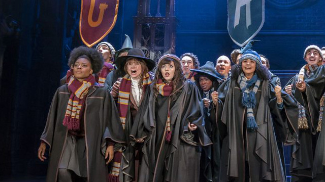 The cast on stage wearing school scarves and wizarding attire in Harry Potter and the Cursed Child