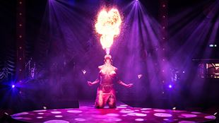 A person breathing fire into the air during a performance of La Clique.