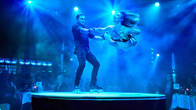 Two roller-skating acrobats perform during La Clique, one standing holding hands with the other as she moves thorugh the air.