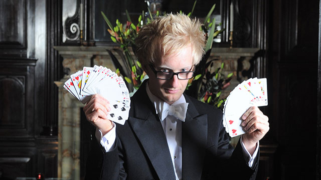 A blond magician holding a pack of cards fanned out in each hand