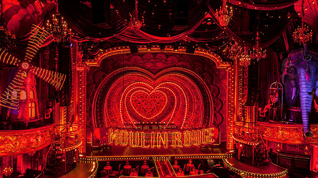 The spectacular Moulin theatre lit up in red featuring the famous red windmill