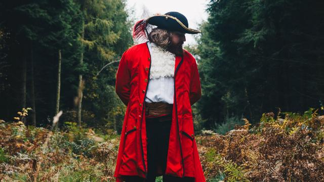 Man dressed as pirate standing in woods.