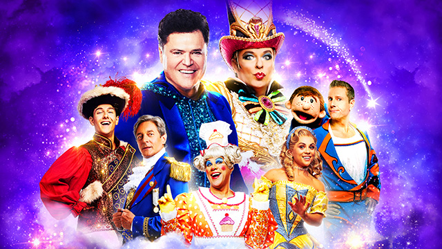 The cast of Pantoland at the London Palladium in costume, with a sparkling blue and purple background.