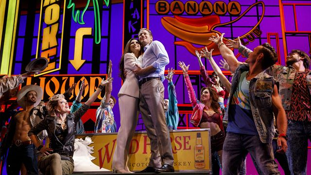 Edward and Vivian embrace centre stage in front of neon signs with the Pretty Woman cast raising their arms up to them.