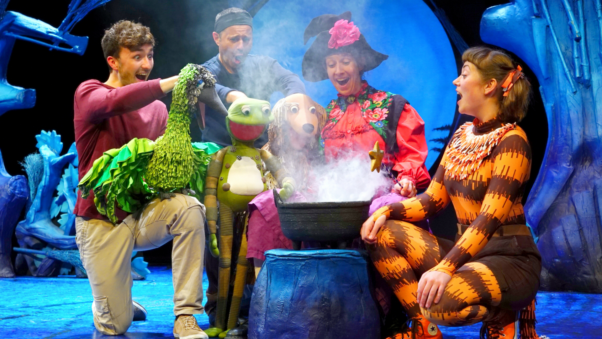 A puppet bird, frog and dog sit around a smoking cauldron with actors dressed as a witch and a cat.
