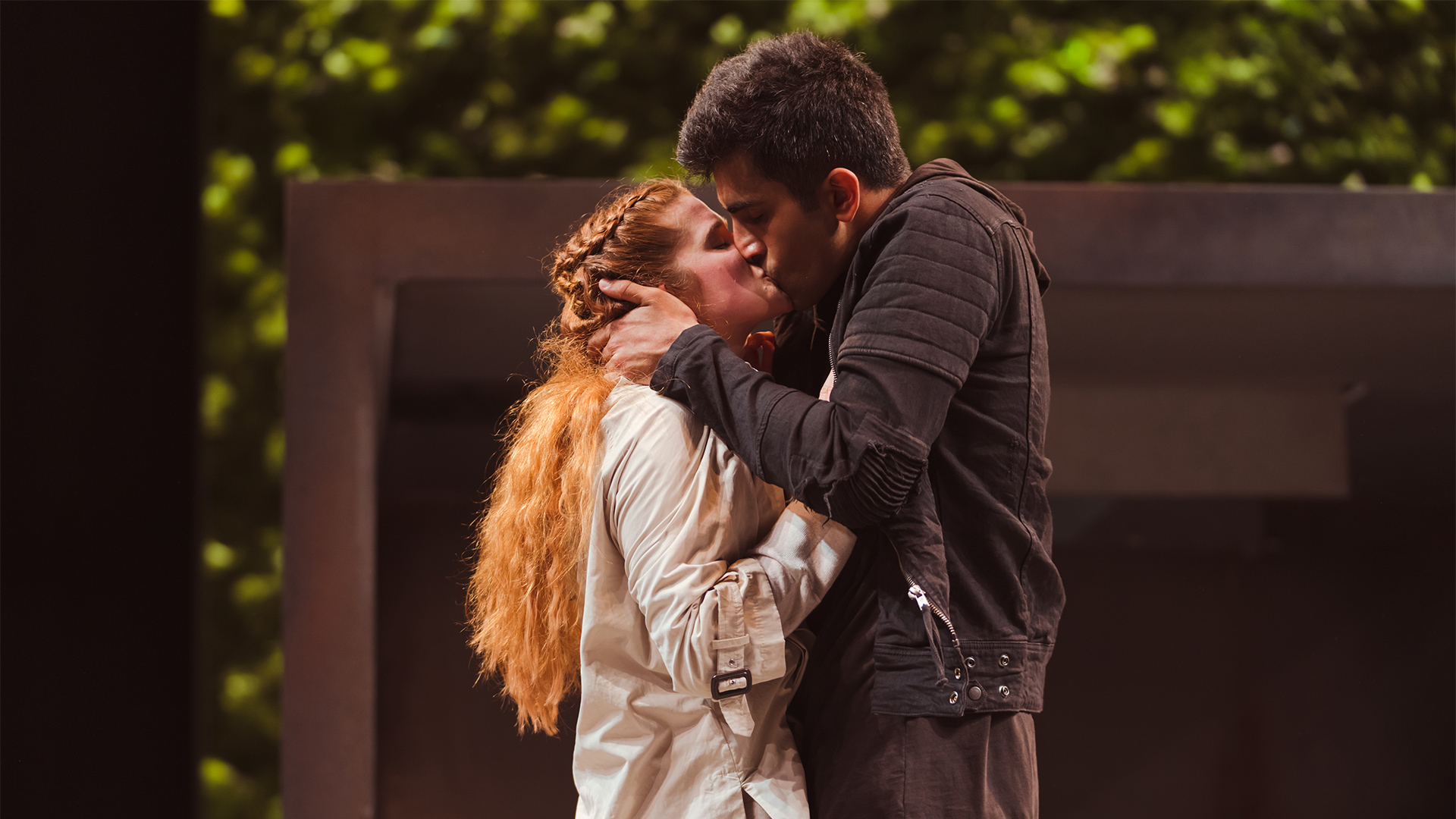 Romeo and Juliet embrace in front of a doorway.