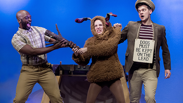 """Three actors on stage against a blue background, one waring a brown dog outfit and fighting over a large stick with another cast member, and the third wearing a sign written """"Dogs must be kept on the lead""""."""