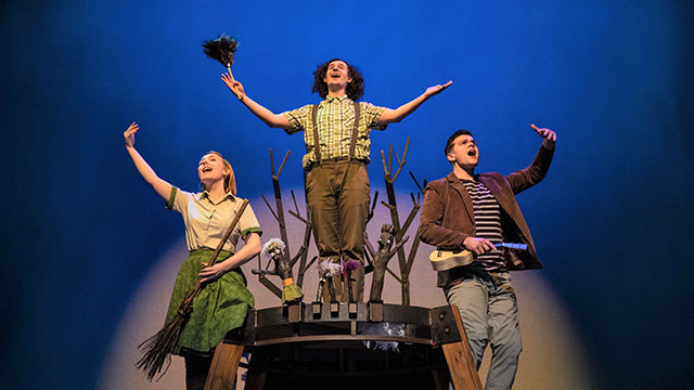 The cast and characters of Stick Man on stage under the spotlight