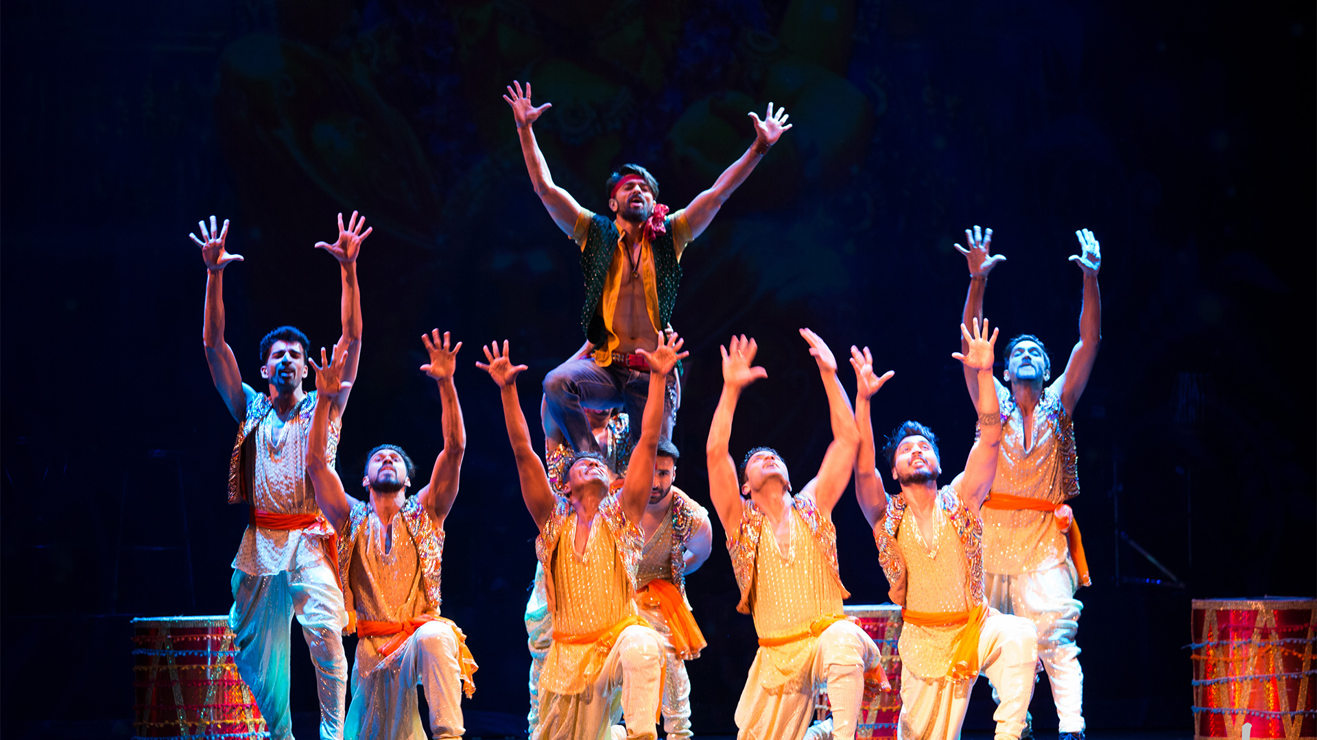 A group of 7 dancers hold their hands in the air during a performance of Taj Express.