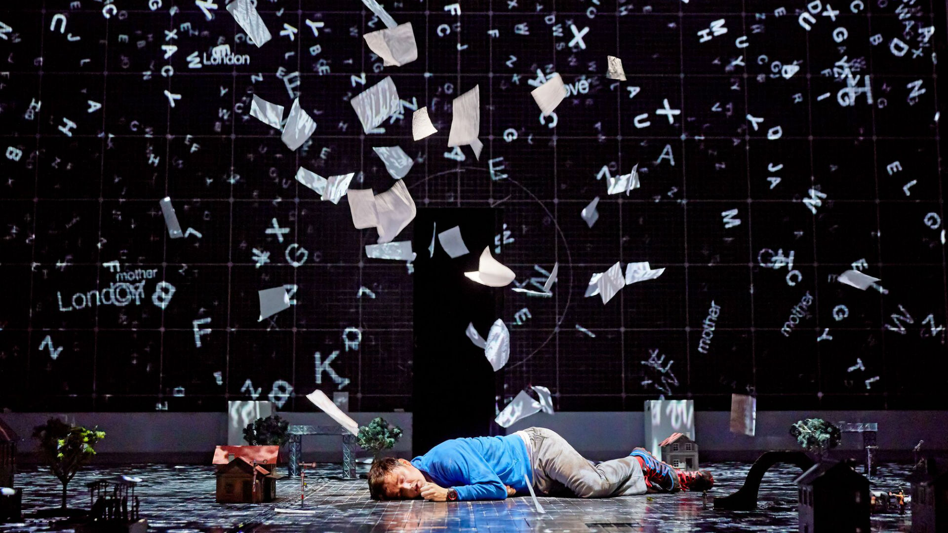 A man is lying on the floor, with papers flying everywhere around him