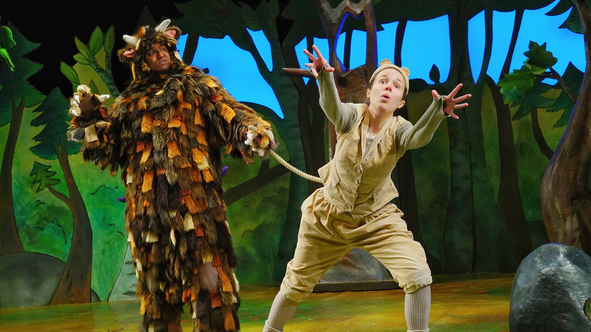 The Gruffalo grabs Mouse's tail on stage.
