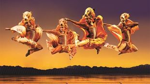 Four dancers leap across the stage in lion costumes in The Lion King.