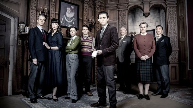 The cast of The Mousetrap are lined up and staring into the camera. with serious faces