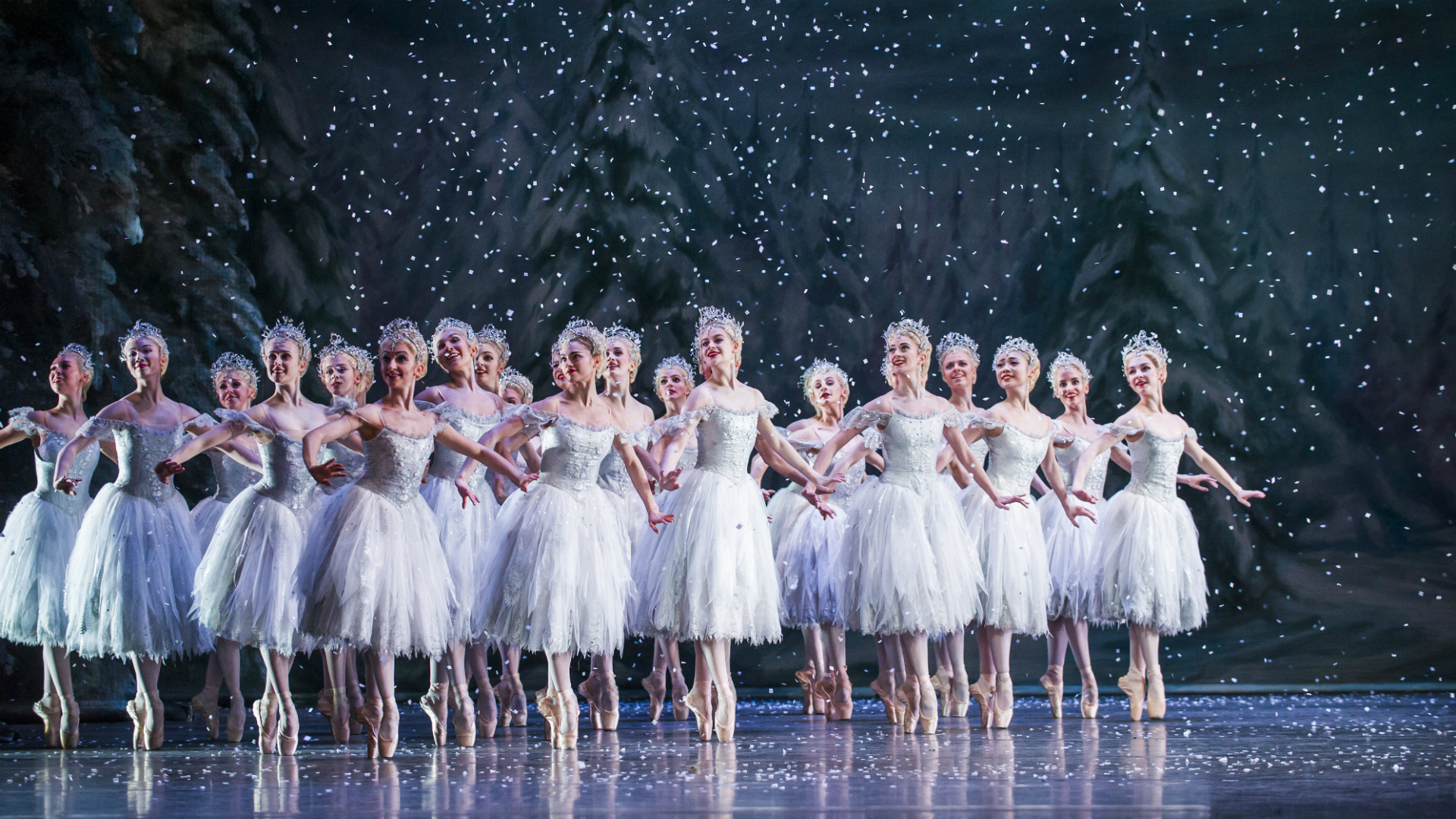 A group of ballerinas dance through falling snow in The Nutcracker.