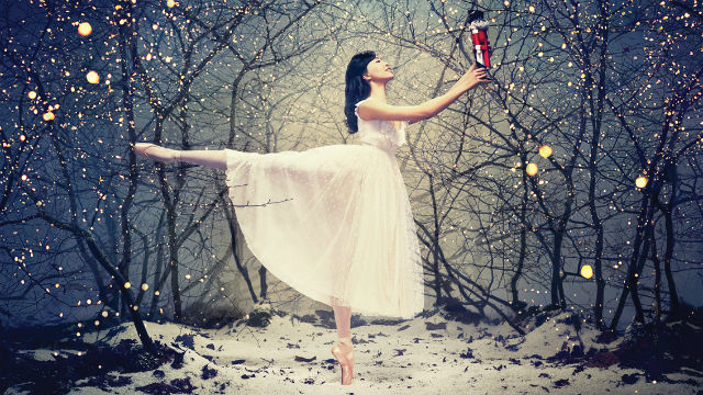 A ballet dancer in a beautiful white dress stands in the middle of a snowy forest holding a nutcracker doll out in front of her.